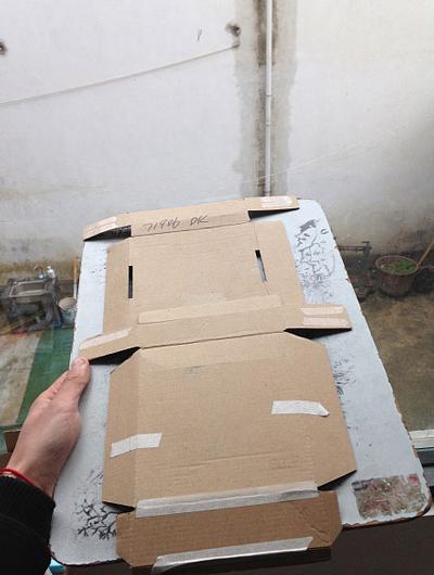 เขาแกะกล่องกระดาษให้เป็นแผ่น แล้วเหน็บกับกระดานรองวาด ที่มา Borepanda.com